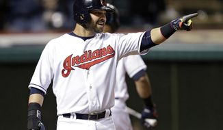 Cleveland Indians' Nick Swisher points to Jason Kipnis after scoring from first on Kipnis' double in the seventh inning of a baseball game against the Kansas City Royals, Wednesday, April 23, 2014, in Cleveland. (AP Photo/Mark Duncan)