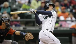 Seattle Mariners' Kyle Seager, right, hits a three-run walkoff home run as Houston Astros catcher Jason Castro looks on in the ninth inning of a baseball game on Wednesday, April 23, 2014, in Seattle. The Mariners won 5-3. (AP Photo/Elaine Thompson)