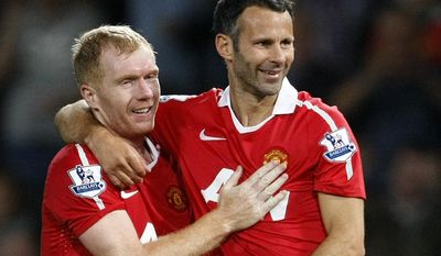FILE - This is a Monday, Aug. 16, 2010 file photo Manchester United's Ryan Giggs, right,  with teammate Paul Scholes after scoring a goal against Newcastle United during their English Premier League soccer match at Old Trafford, Manchester, England.  Ryan Giggs will be assisted by former teammates Paul Scholes, Nicky Butt and Phil Neville during his spell as interim manager of Manchester United following the dismissal of David Moyes. (AP Photo/Tim Hales, File)