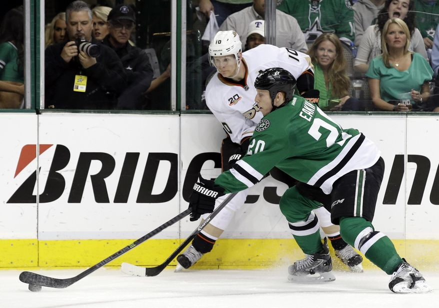 Dallas Stars' Cody Eakin (20) attempts to gain control of the puck under pressure from Anaheim Ducks' Corey Perry (10) during the second period of Game 4 of a first-round NHL hockey Stanley Cup playoff series, Wednesday, April 23, 2014, in Dallas. (AP Photo/Tony Gutierrez)