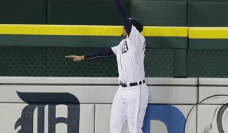 Detroit Tigers left fielder J.D. Martinez jumps but can't catch a grand slam by Chicago White Sox's Marcus Semien during the seventh inning of a baseball game in Detroit, Wednesday, April 23, 2014. (AP Photo/Carlos Osorio)