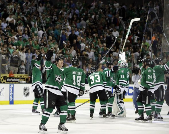 Dallas Stars' Cody Eakin (20) and the rest of the time lift their sticks as they acknowledge cheers from fans following a 4-2 win in Game 4 of a first-round NHL hockey Stanley Cup playoff series against the Anaheim Ducks, Wednesday, April 23, 2014, in Dallas. (AP Photo/Tony Gutierrez)