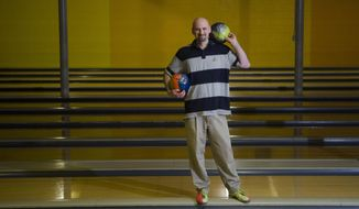 In this photo taken on March 26, 2014, Jason Hicks, 35, poses for a photo at the Clio Bowling Arcade in Clio, Mich. The  Flint-area bowler is taking aim at the Guinness World Records mark for most strikes in a minute. The Flint Journal reports that last month Hicks unofficially tied the record, getting 12 at the Clio Bowling Acrade. The 35-year-old is planning to give it another try May 2 at the bowling alley that's owned by his family. (AP Photo/The Flint Journal, Samuel Wilson) LOCAL TV OUT; LOCAL INTERNET OUT