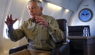 U.S. Defense Secretary Chuck Hagel speaks to the media aboard a plane en route for his trip to Mexico City Wednesday, April 23, 2014.  (AP Photo/Shannon Stapleton, Pool)