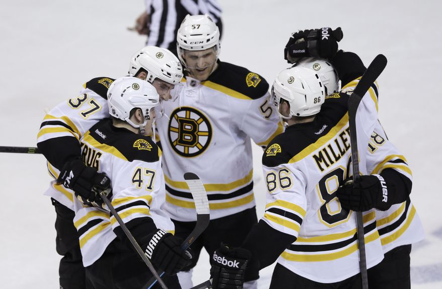 Boston Bruins, clockwise from foreground left, Torey Krug (47), Patrice Bergeron, Justin Florek, Reilly Smith  and Kevan Miller (86) celebrate Krug's goal during the second period of Game 4 of a first-round NHL hockey playoff series against the Detroit Red Wings in Detroit, Thursday, April 24, 2014. (AP Photo/Carlos Osorio)