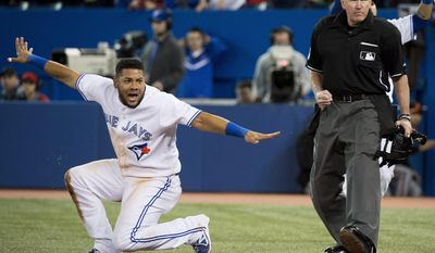 Toronto Blue Jays' Melky Cabrera, left, reacts after being called out by home plate umpire Mike Winters, right, on a tag by Baltimore Orioles catcher Matt Wieters during the first inning of a baseball game in Toronto on Thursday, April 24, 2014. (AP Photo/The Canadian Press, Nathan Denette)