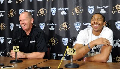 Colorado head coach Tad Boyle, left, joins Spencer Dinwiddie at a news conference on Thursday, April 24, 2014, in Boulder, Colo. Dinwiddie announced that he is skipping his senior season and will declare for the NBA draft. (AP Photo/The Daily Camera, Cliff Grassmick) NO SALES