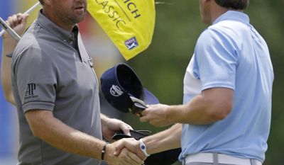 Peter Hanson, left, of Sweden, shakes hands with Ricky Barnes on the ninth green as they finished the opening round of the Zurich Classic golf tournament at TPC Louisiana in Avondale, La., Thursday, April 24, 2014. (AP Photo/Gerald Herbert)