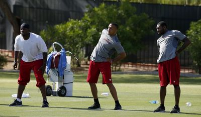 From left to right, Arizona Cardinals' Marcus Benard, Michael Floyd and Antonio Cromartie stretch during the first phase of the voluntary offseason training program at the NFL football team's training facility on Thursday, April 24, 2014, in Tempe, Ariz. (AP Photo/Ross D. Franklin)