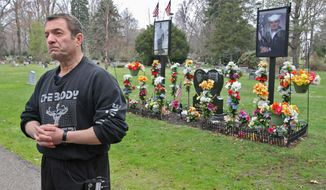 This photo taken on Wednesday, April 23, 2014, shows Fred Molai at the gravesite of his son, Adam, at Standing Rock Cemetery in Kent, Ohio. Molai is embroiled in a legal fight with a cemetery that contends he is breaking the rules with 8-foot high poles bearing large photographs, part of an elaborate, flower-shrouded shrine at the grave of his adult son. (AP Photo/Akron Beacon Journal, Phil Masturzo) MANDATORY CREDIT