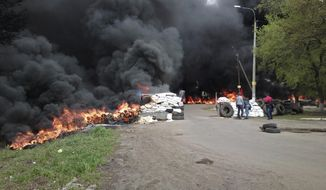 "Black smoke billows from burning tires at a checkpoint following an attack by Ukrainian troops outside Slovyansk, Ukraine, Thursday, April 24, 2014. Ukrainian government troops moved against pro-Russia forces in the east of the country on Thursday and killed at least two of them in clashes at checkpoints manned by the insurgents, the government and insurgents said. Russian President Vladimir Putin decried what he described as a ""punitive operation."" (AP Photo/Mika Velikovskiy)"