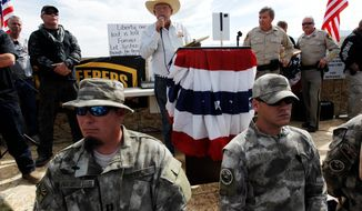 ** FILE ** Rancher Cliven Bundy, middle, addresses his supporters along side Clark County Sheriff Doug Gillespie, right, on April 12, 2014. Bundy informed the public that the BLM has agreed to cease the roundup of his family's cattle. (AP Photo/Las Vegas Review-Journal, Jason Bean)