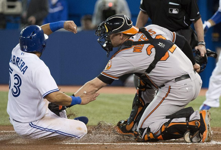 Toronto Blue Jays' Melky Cabrera, left, is tagged out at home plate by Baltimore Orioles catcher Matt Wieters during the first inning of a baseball game in Toronto on Thursday, April 24, 2014. (AP Photo/The Canadian Press, Nathan Denette)