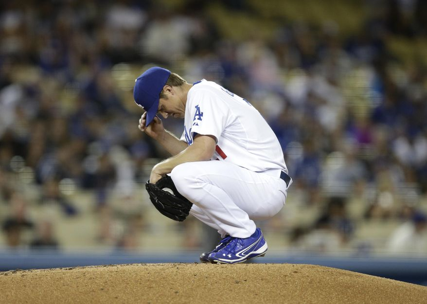 Los Angeles Dodgers pitcher Zack Greinke adjusts his hat while squatting on the mound during the fourth inning of a baseball game against the Philadelphia Phillies on Wednesday, April 23, 2014, in Los Angeles. (AP Photo/Jae C. Hong)