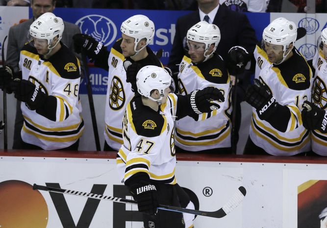 Boston Bruins defenseman Torey Krug celebrates his goal with teammates during the second period of Game 4 of a first-round NHL hockey playoff series against the Detroit Red Wings in Detroit, Thursday, April 24, 2014. (AP Photo/Carlos Osorio)