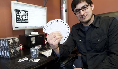 "ADVANCE FOR MONDAY, APRIL 28 AND THEREAFTER - Winona, Minn., graphic designer Jose Pelaez, seen in an April 9, 2014 photo, created the game ""Cards vs. Dice: Strategically Lucky,"" which sells on Amazon.com. (AP Photo/Winona Daily News, Andrew Link)"