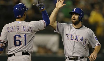 Texas Rangers' Robinson Chirinos (61) congratulates Kevin Kouzmanoff, right, after Kevin Kouzmanoff scored against the Oakland Athletics in the eighth inning of a baseball game Monday, April 21, 2014, in Oakland, Calif. Kouzmanoff scored on a single by Donnie Murphy. (AP Photo/Ben Margot)