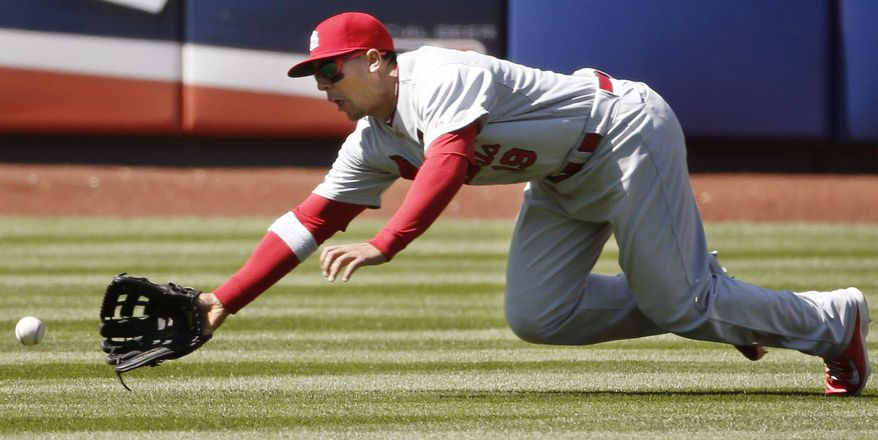 St. Louis Cardinals center fielder Jon Jay (19) comes up short fielding Danile Murphy's sixth-inning RBI double in a baseball game against the New York Mets in New York, Thursday, April 24, 2014. (AP Photo/Kathy Willens)