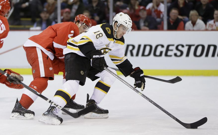 Boston Bruins right wing Reilly Smith (18) controls the puck ahead of Detroit Red Wings defenseman Brendan Smith during the first period of Game 4 of a first-round NHL hockey playoff series in Detroit, Thursday, April 24, 2014. (AP Photo/Carlos Osorio)