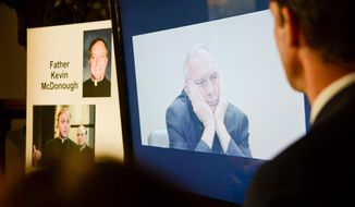 Attorney Mike Finnegan, right, watchs a video recording of a deposition given earlier by Father Kevin McDonough during a news conference in St. Paul, Minn. on Thursday, April 24, 2014. Lawyers for alleged victims of sexual abuse by priests released a video deposition Thursday given by McDonough, the archdiocese's former vicar general, who handled any complaints of abuse. (AP Photo/ Pioneer Press, Ben Garvin)