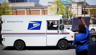** FILE ** A U.S. Post Office driver gestures while passing a protest by fellow postal employees outside a Staples store, Thursday, April 24, 2014, in Atlanta. Thousands of postal workers picketed outside Staples stores nationwide Thursday to protest a pilot program that allows the office supply chain to handle U.S. mail. (AP Photo/David Goldman)