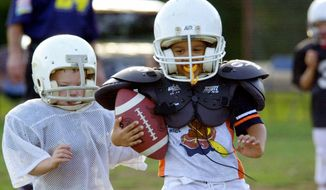 **FILE** Brandon Graham (left) chases Michael Bashaw as he breaks through the line of scrimmage during a practice session of the pee-wee team of the Mighty Mite football league in Chickasha, Okla., on Aug. 30, 2001. (Associated Press)