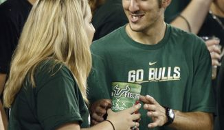 **FILE** Two University of South Florida students take turns drinking from a cup during a college football game in Tampa, Fla., on Sept. 19, 2009. (Associated Press)