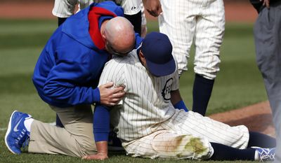 Chicago Cubs right fielder Justin Ruggiano is tended to during the ninth inning of a baseball game against the Arizona Diamondbacks at Wrigley Field in Chicago on Wednesday, April 23, 2014. (AP Photo/Andrew A. Nelles)