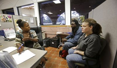 In this Tuesday, April 8, 2014 photo, Community Hope Center caseworker Mia Brennon, left, helps in finding Anthony and Candice Johnson housing in Kissimmee, Fla. (AP Photo/John Raoux)