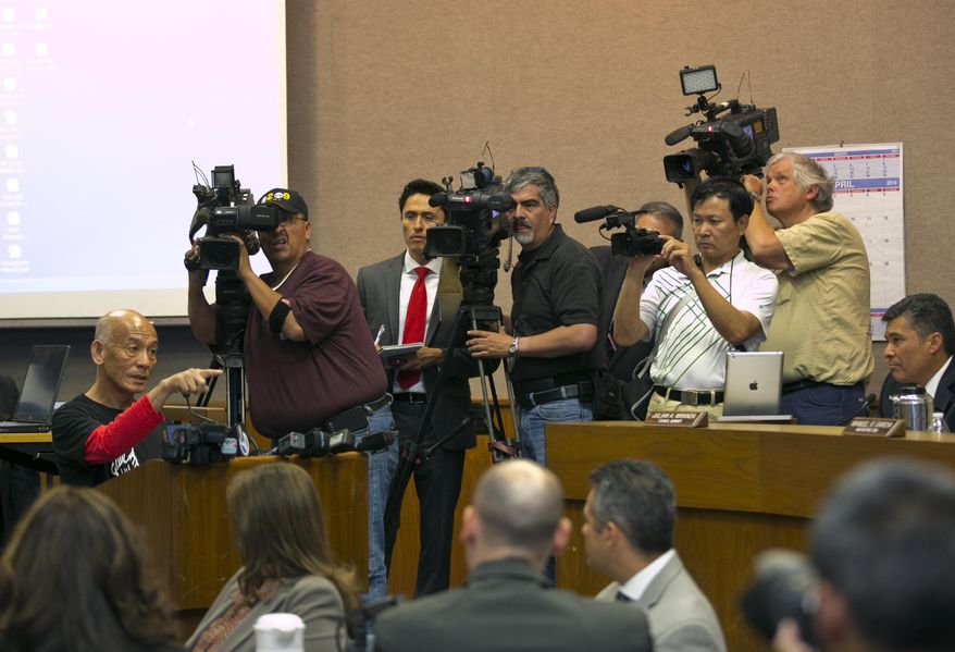 Sriracha hot sauce founder David Tran, at podium, left, addresses a city council meeting in Irwindale, Calif., Wednesday, April 23, 2014. The city of Irwindale is suing the maker of Sriracha hot sauce and last week the Los Angeles suburb tentatively voted to declare the bottling plant a public nuisance. Irwindale City Attorney Fred Galante says relocating seems extreme and the city only wants to see the smell issue addressed. (AP Photo/Damian Dovarganes)