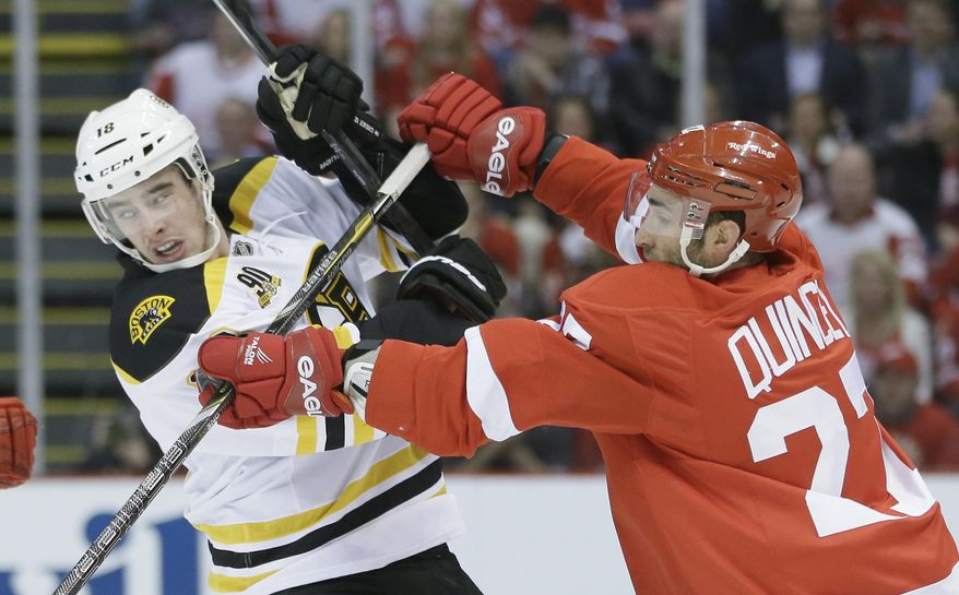 Detroit Red Wings defenseman Kyle Quincey (27) checks Boston Bruins right wing Reilly Smith during the first period of Game 4 of a first-round NHL hockey playoff series in Detroit, Thursday, April 24, 2014. (AP Photo/Carlos Osorio)