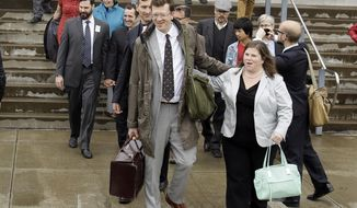 Plaintiffs, attorneys and supporters walk out of federal court where a federal judge heard oral arguments in two cases challenging Oregon's ban on same-sex marriage in Eugene, Ore., Wednesday, April 23, 2014. Judge Michael McShane did not say which way he was leaning, but his questioning focused heavily on how he should apply precedents from higher courts. (AP Photo/Don Ryan)