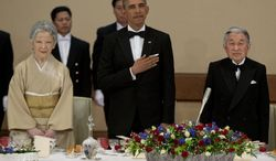 President Barack Obama stands with his hand over his heart as the National Anthem is played with Japanese Emperor Akihito, right, and his wife Empress Michiko, left, during a state dinner at the Imperial Palace in Tokyo, Thursday, April 24, 2014. (AP Photo/Carolyn Kaster)