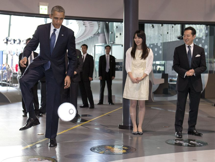 President Barack Obama kicks a ball passed to him by a robot namesd ASIMO, an acronym for Advanced Step in Innovative Mobility, as he attends a youth science event at the National Museum of Emerging Science and Innovation, known as the Miraikan, in Tokyo, Thursday, April 24, 2014. At right is Japanese astronaut Mamoru Mohri, and director of the Museum. (AP Photo/Carolyn Kaster)