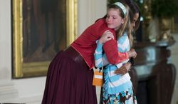 """First lady Michelle Obama hugs Charlotte Bell, 10, after she handed Mrs. Obama her dad's resume during the White House's annual """"Take Our Daughters and Sons to Work Day,"""" Thursday, April 24, 2014, in the East Room of the White House in Washington. The girl in the front row at Thursday's event told the first lady that her dad had been out of work for three years. Then the girl popped up to hand Mrs. Obama her dad's resume saying """"My dad's been out of a job for three years and I wanted to give you his resume."""" (AP Photo/ Evan Vucci)"""