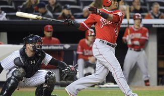 Los Angeles Angels' Erick Aybar, right, hits a three-run home run as New York Yankees catcher Brian McCann, left, looks on during the seventh inning of a baseball game on Friday, April 25, 2014, at Yankee Stadium in New York. (AP Photo/Bill Kostroun)