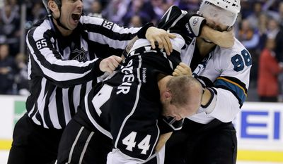 Linesman Pierre Racicot, left, tries to break up a fight between Los Angeles Kings defenseman Robyn Regehr and San Jose Sharks right wing Brent Burns, right, during the third period in Game 4 of an NHL hockey first-round playoff series in Los Angeles, Thursday, April 24, 2014. (AP Photo/Chris Carlson)