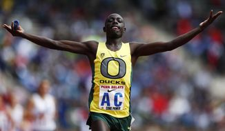 Oregon's Edward Cheserek raises his hands after crossing the finish line during the College Men's Distance Medley Championship of America at the Penn Relays athletics meet, Friday, April 25, 2014, in Philadelphia. Oregon won with a time of 9:25.40. (AP Photo/Matt Rourke)