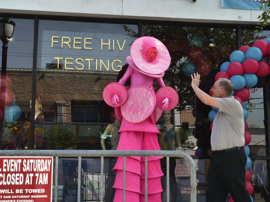 In a Saturday April 19, 2014 photo, The PinkHoopla, played by Patric Daddy, is greeted by a pedestrian at th grand opening of the  Out of the Closet Thrift Store in Dallas. The stores are part of the AIDS Healthcare Foundation, and 96 cents of every dollar earned  goes into supporting AHF clinics serving nearly 300,000 people worldwide. (AP Photo/The Dallas Morning News, Ron Baselice)