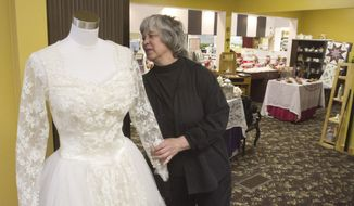ADVANCE FOR USE SUNDAY, APRIL 27 - In this photo taken on Monday, April 14, 2014, Hamburg Museum director Suzanne Hines adjusts a dress display at the historic museum in Hamburg, Mich., that may be forced to close its doors due to lack of funding to meet its operational costs. (AP Photo/Livingston County Daily Press & Argus, Gillis Benedict) NO SALES