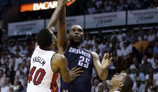 Charlotte Bobcats' Al Jefferson (25) shoots over Miami Heat's Udonis Haslem (40) and Mario Chalmers (15) during the second half in Game 2 of an opening-round NBA basketball playoff series, Wednesday, April 23, 2014, in Miami. The Heat defeated the Bobcats 101-97. (AP Photo/Lynne Sladky)