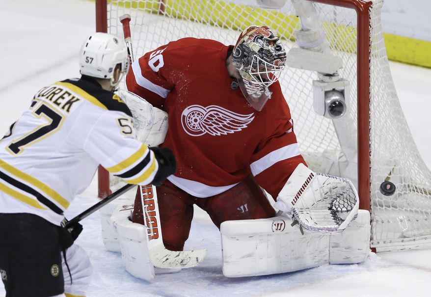 Detroit Red Wings goalie Jonas Gustavsson (50) deflects a shot by Boston Bruins left wing Justin Florek (57) during the third period of Game 4 of a first-round NHL hockey playoff series in Detroit, Thursday, April 24, 2014. (AP Photo/Carlos Osorio)