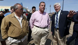 Seaside Park Mayor Robert Matthies, right, points in the direction of the reconstruction of his town's beach-front boardwalk while walking with New Jersey Gov. Chris Christie, center, and Seaside Heights Mayor William Akers, Friday, April 25, 2014, in Seaside Heights, N.J. Christie visited the boardwalk to see progress following last September's massive fire that burned down the Seaside Park side of the boardwalk. Previously, the boardwalk had been rebuilt following Superstorm Sandy. Investigators determined the fire started in wiring under the boardwalk in Seaside Park that had been damaged by exposure to storm water from Sandy. (AP Photo/Julio Cortez)