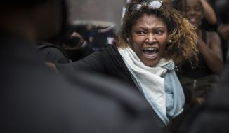 A woman shouts at police officers as residents of Pavao-Pavaozinho slum clash with riot police during a protest against the death of Douglas Rafael da Silva Pereira after his burial in Rio de Janeiro, Brazil, Thursday, April 24, 2014. The protest followed the burial of Douglas Pereira, whose shooting death sparked clashes Tuesday night between police and residents of the Pavao-Pavaozinho slum. (AP Photo/Felipe Dana)