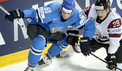 FILE - In this Tuesday, May 14, 2013 file photo, Finland's Juhamatti Aaltonen, left, vies for the puck with Latvia's Ralfs Freibergs during the 2013 Ice Hockey IIHF World Championships Group B preliminary round match in Helsinki. Two months after the closing ceremony, the Sochi Olympics broke a Winter Games record Friday, April 25, 2014 when a Latvian hockey player became the eighth athlete disqualified for a positive doping test. Ralfs Freibergs was retroactively kicked out of the games by the IOC after being found guilty of a steroid offense, the third hockey player and second from Latvia caught for doping in Sochi. (AP Photo/Lehtikuva, Jussi Nukari, File) FINLAND OUT