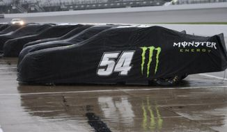 Covered Sprint cup cars wait out the rain  at Richmond International Raceway in Richmond, Va., Friday, April 25, 2014.  Qualifying for Saturday's Sprint cup race was cancelled.  (AP Photo/Zach Gibson)