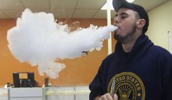 ** FILE ** In this April 3, 2014, photo, Joshua Pilatz blows a cloud of vapor after inhaling on his electronic cigarette, which has a powerful battery, at Vapors, a new shop in Danville, Ill. (AP Photo/Commercial-News, Mary Wicoff)
