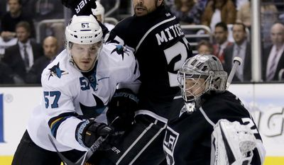 Los Angeles Kings goalie Jonathan Quick, right, blocks a shot by San Jose Sharks right wing Adam Burish, left, as Willie Mitchell looks on during the first period in Game 4 of an NHL hockey first-round playoff series in Los Angeles, Thursday, April 24, 2014. (AP Photo/Chris Carlson)