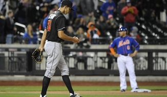 Miami Marlins relief pitcher Steve Cishek (31) reacts on the mound after giving up a double to New York Mets' Kirk Nieuwenhuis that advanced Omar Quintanilla, right, to third base in the ninth inning of a baseball game at Citi Field on Friday, April 25, 2014, in New York. 2The Mets won 4-3. (AP Photo/Kathy Kmonicek)