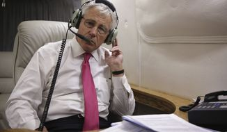 **FILE** U.S. Defense Secretary Chuck Hagel talks to South Korean Defense Minister Kim Kwan-jin on the phone from his aircraft after he finished the last stop in Ulan Bator, Mongolia, of his Asian Pacific trip April 10, 2014. (AP Photo/Alex Wong, Pool)